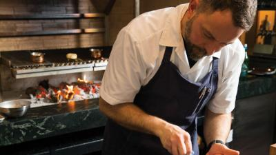 Chef Eric Anderson puts the finishing touches on a plate of duck, one of his star proteins.