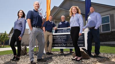 HOME SWEET HOME. Hayden Homes President Steve Klingman, center, standing behind the sign, with, from left, Gina Donangelo, Rees Wasney, Mike Moore, Patti Murphy and Ben McGerty.