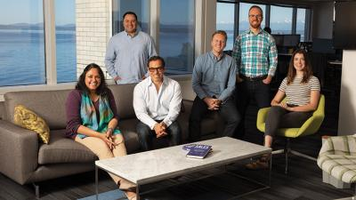 REAL DEAL. Outreach CEO  Manny Medina, seated third from left, with, from right, Emilee Smalley, Ryan Jander, Stephen Farnsworth, Mario Espinoza and Preetha Chatterjee.